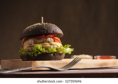 Concept: restaurant menus, healthy eating, homemade, gourmands, gluttony. Trendy burger with chicken in black bun with ingredients on messy vintage wooden background.