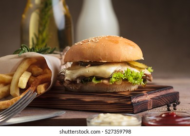 Concept: restaurant menus, healthy eating, homemade, gourmands, gluttony. Classic burger with beef with ingredients and french fries on messy vintage wooden background.