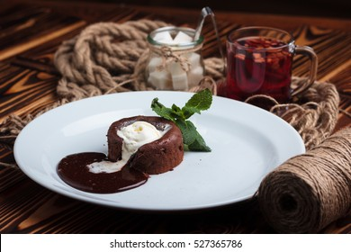 Concept: restaurant menus, healthy eating, homemade, gourmands, gluttony. White plate with chocolate fondant and ice cream on a messy vintage wooden background.