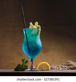 Concept: restaurant menus, healthy eating, homemade, gourmands, gluttony. Blue Lagoon Cocktail on gritty vintage background.