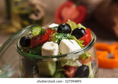 Concept: restaurant menus, healthy eating, homemade, gourmands, gluttony. Greek salad served in glass jar with ingredients on weathered sackcloth background.