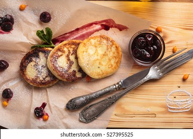 Concept: restaurant menus, healthy eating, homemade, gourmands, gluttony. Cheese pancakes with cherry sauce served on paper with ingredients on vintage wooden table. Top-down view