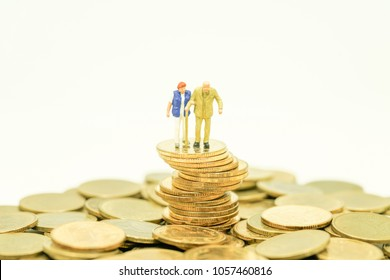 Concept of retirement planning. Miniature people: Old couple figure standing on top of unstable coin stack.