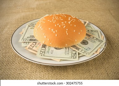Concept for rich and greedy - Burger buns stuffed with money placed in a plate or a grunge table cloth