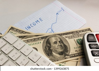 concept of the right business strategy that brings a stable income. paper sheet with handwriting inscription MY INCOME, the arrow showing revenue growth, a fan of hundred dollar bills and calculator