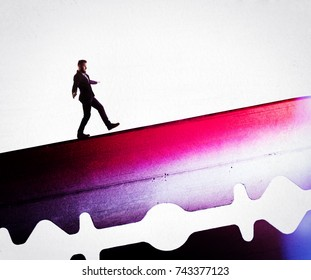 The concept of risk. A man in a business suit is walking along the razor's blade.