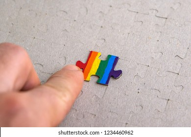 concept of the role of the LGBT community in society: puzzle with the coloring of the flag of sexual minorities is embedded in the overall picture of the social system, short focus