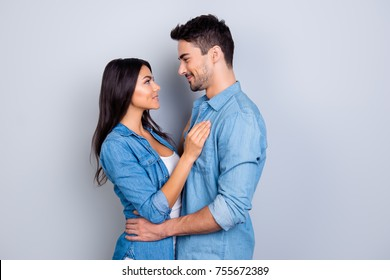 Concept of romantic relationship between man and woman. Girl with bronze skin woman and handsome man are standing face to face and are going to kiss each other, isolated on grey background