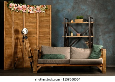 Concept of rustic interior. Wooden folding screen, sofa and shelving with grunge painted wall