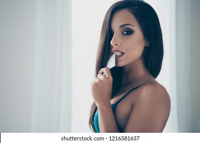 Concept of safe sex life. Profile side view photo of gorgeous adorable brunette lady in blue lace holding silver pack with preservative in tooth look at camera on cozy house with modern interior