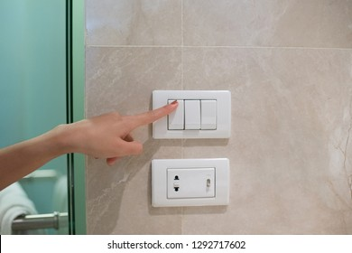 concept save energy. woman hand turning off switch