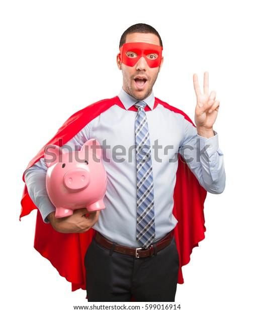 Concept of a saver super businessman with a piggy bank