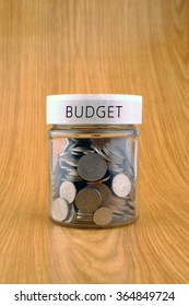 concept of saving, coins in jar with buget label on wooden background.