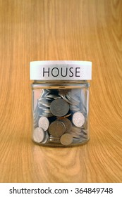 concept of saving, coins in jar with house label on wooden background.
