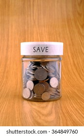 concept of saving, coins in jar with save label on wooden background.