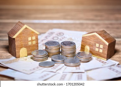 The concept of saving money to buy a house. (there is a house made of wood and money is placed at the account desk)