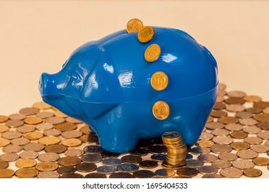 Concept saving money. Coins thrown into the blue piggy bank. Biznes and economy.