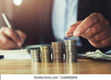 concept saving money. hand holding coins putting stack on table in office