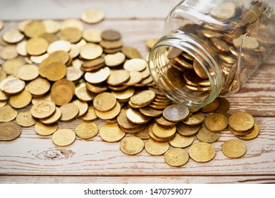 Concept for savings money. Coins in a glass jar and scattered around, on white wooden table top..