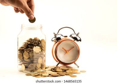 Concept for savings where time is money. Coins in a glass jar and scattered around with alarm clock, isolated on white..
