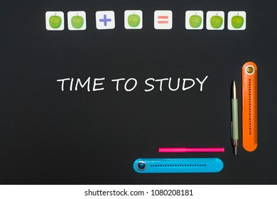 Concept school, black art table with stationery supplies with text time to study on blackboard