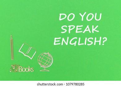 concept school for kids, text do you speak english, school supplies wooden miniatures on green backboard