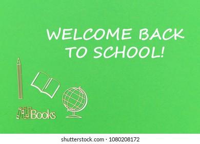 concept school for kids, text welcome back to school, school supplies wooden miniatures on green backboard
