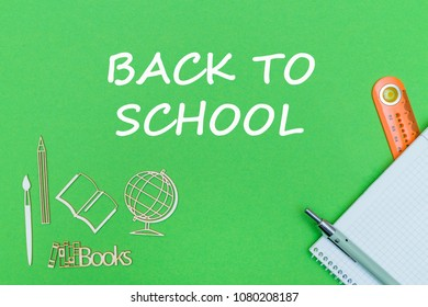 concept school, text back to school, school supplies, notebook, ruler and pen on green backboard
