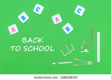 concept school, text back to school, school supplies wooden minitures, abc letters on green backboard