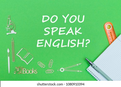 concept school, text do you speak english, school supplies wooden miniatures, notebook with ruler and pen on green backbord