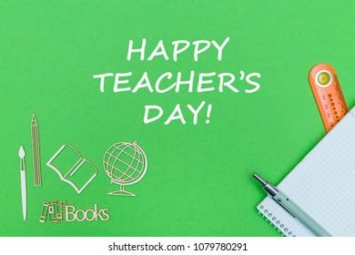 concept school, text happy teacher's day, school supplies, notebook, ruler and pen on green backboard