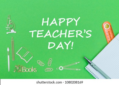 concept school, text happy teacher's day, school supplies wooden miniatures, notebook with ruler and pen on green backbord
