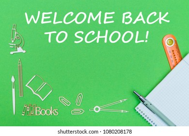concept school, text welcome back to school, school supplies wooden miniatures, notebook with ruler and pen on green backbord