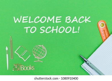 concept school, text welcome back to school, school supplies, notebook, ruler and pen on green backboard