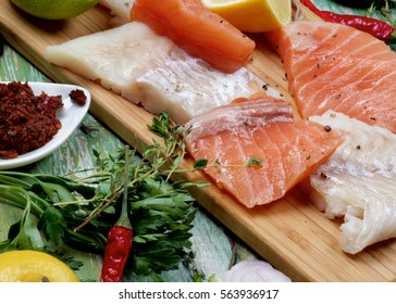 Concept of Seafood with Big Slices of Raw Fillet of Salmon and Cod, Greens, Spices and Lemon closeup on Cracked Wooden background