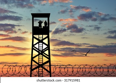 Concept of security. Silhouette barbed wire and a watchtower with soldiers at sunset