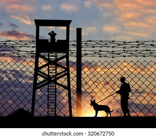 Concept of security. Silhouette of a lookout tower and a guard with a dog on the background of the fence with barbed wire at sunset