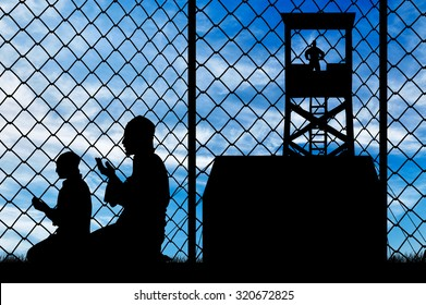 Concept of security. Silhouette of praying refugees and barbed wire fence on the background of the observation tower and stalls