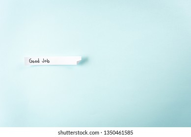 """Concept of sending a positive message to employee. Paper with the word """"good job"""" on blue background with empty space for text."""