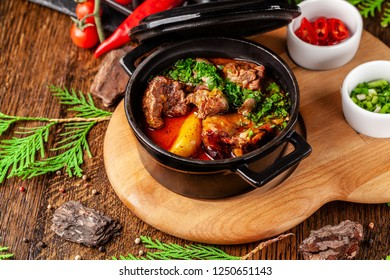 The concept of Serbian cuisine. Juicy baked beef in its own juice with potatoes, vegetables and greens. Serve in an iron fire on a wooden board.