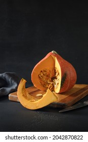 Concept sesonal atumn harvest with organic cutted pumpkin on a black background. Thanksgiving Day or Halloween Party. Vertical format.