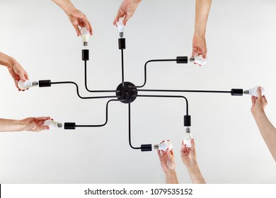 Concept of shared values, or shared purpose on example of united actions during teamwork when replacing LED lamps in a ceiling lighting.