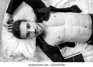 Concept of shirtless, handsome, man lying in bed listening to earphones audiobook, spoken word