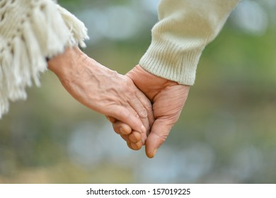 Concept shoot of friendship and love of man and woman: two hands over nature