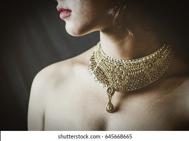 concept shoot with a model wearing a jewellery gold neckpiece at a studio