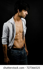 concept shoot with smart asian guy with abs wearing a shirt posing on a black background