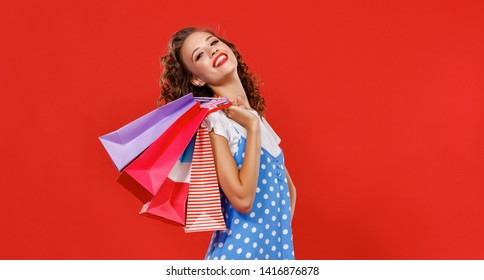 concept of shopping purchases and sales of happy young girl with packages   on red background