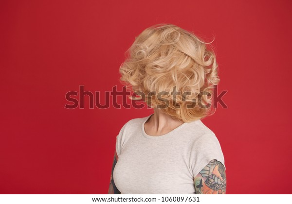 Concept shot of blonde girl looks back and show her curly hair. Isolated over red background