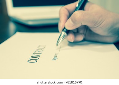 A concept of signing a contract holding a pen.