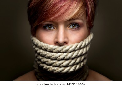Concept of silence, gag and domination. Portrait of a beautiful woman wrapped in a rope on her face.